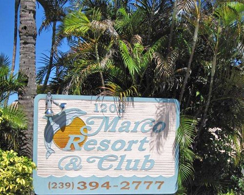 Signboard of Marco Resort And Club surrounded by palm trees.