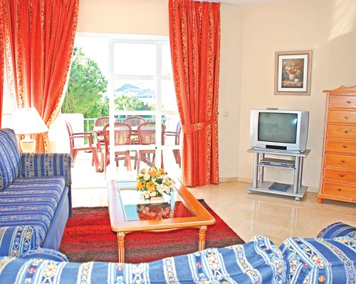 A well furnished living room with a television and balcony with patio furniture.
