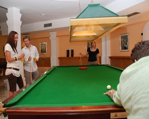 Indoor recreation room with view of people playing pool at the pool table.