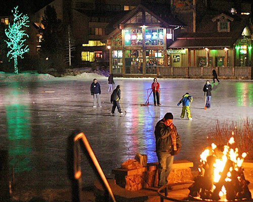 View of Village Square At Copper Mountain Resort with people playing snow hockey alongside campfire.