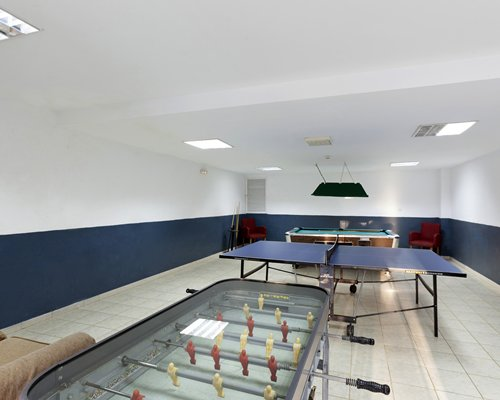An indoor recreation room with foosball ping pong and pool table.
