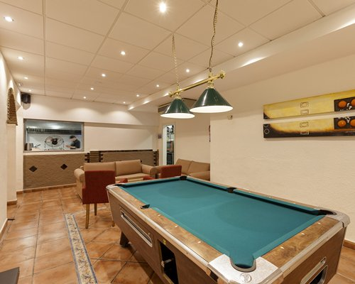 An indoor recreational area with pool table alongside a living room.
