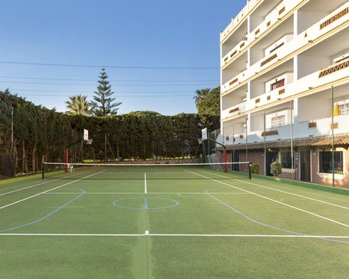 An outdoor tennis court alongside the multi story units.