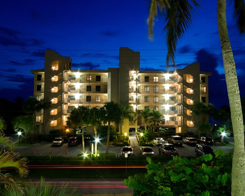 An exterior view of multi story resort units with a parking lot at night.