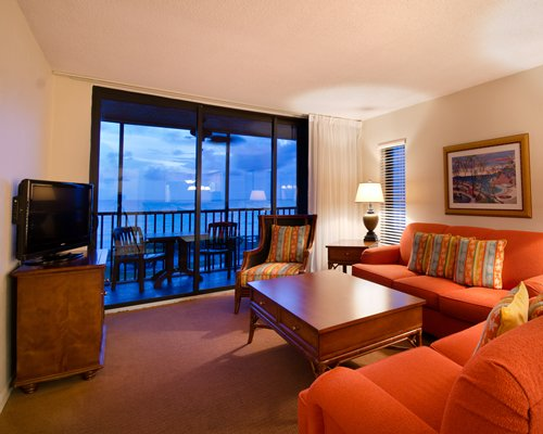 A well furnished living room with television sofas and a balcony with the ocean view.