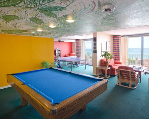 An indoor recreation room with pool table and the ping pong table.