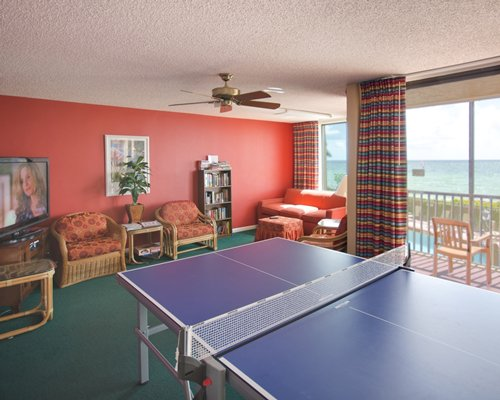 An indoor recreation room with ping pong table television and a balcony with the ocean view.
