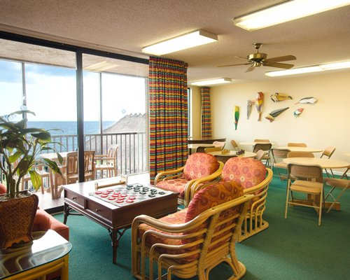 An indoor recreation room and a balcony with the ocean view.