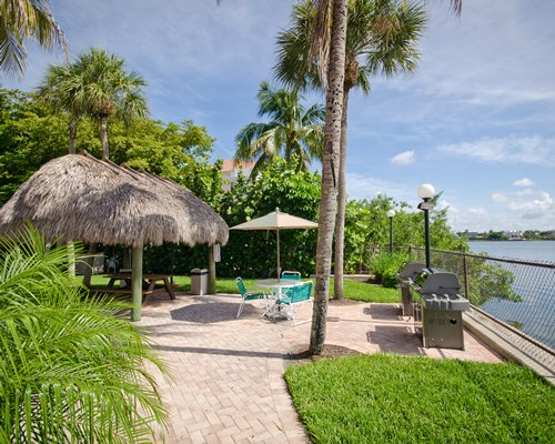 Scenic outdoor thatched covered picnic area with barbecue grill alongside the ocean.