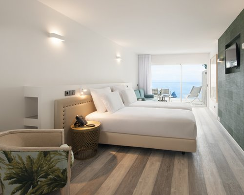 A bedroom with two queen beds and an ocean vi