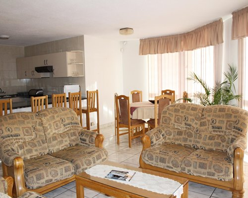 A well furnished living room with a dining area open plan kitchen and breakfast bar.