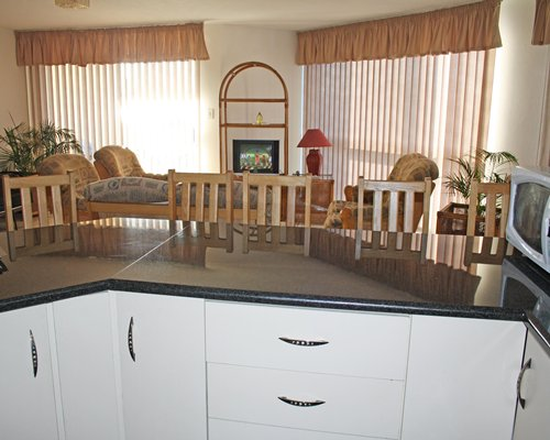 A well furnished living room with television alongside the kitchen with breakfast bar.