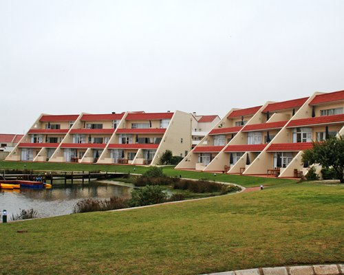A scenic exterior view of multi story units alongside the waterfront.