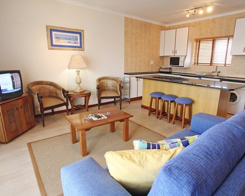 A well furnished living room with a television open plan kitchen and breakfast bar.