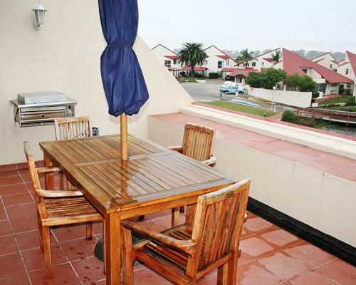 Balcony with patio furniture umbrella and barbecue grill.