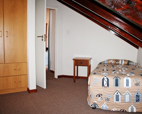 A well furnished bedroom with twin bed and stairway.