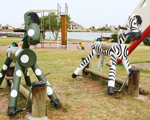 A scenic outdoor children's play area alongside the waterfront.