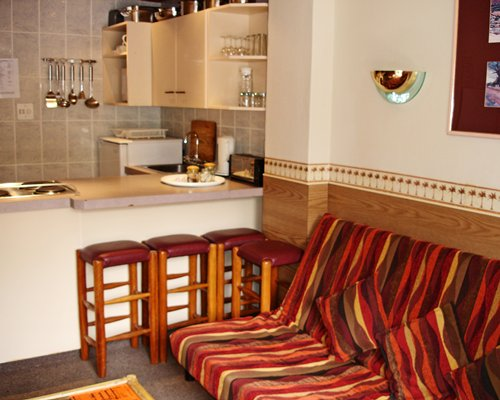 A well equipped kitchen with breakfast bar and sofa.