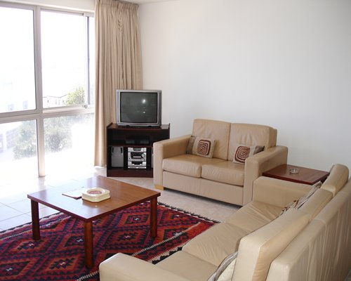 A well furnished living room with a television double pull out sofa and an outside view.