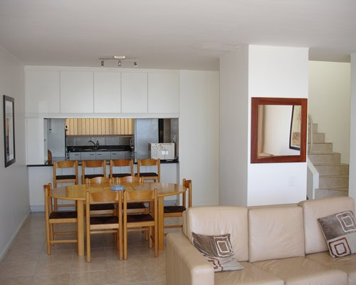 An open plan living room with a wooden dining and kitchen area alongside the staircase.