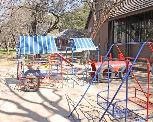 An outdoor kids playscape alongside resort.