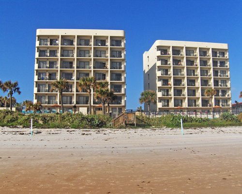 An exterior view of multi story resort units alongside the beach.