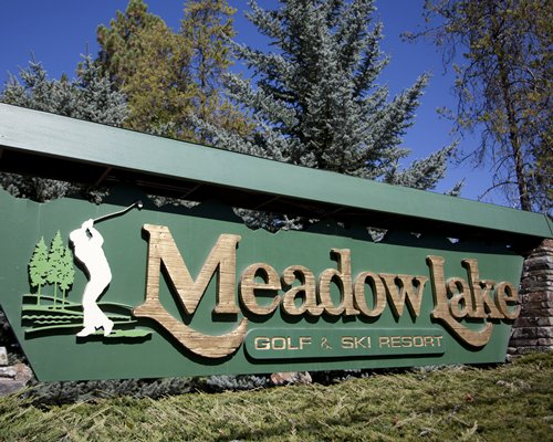Signboard of Meadow Lake Golf Resort surrounded by wooded area.