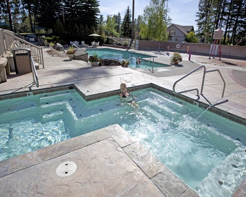Outdoor swimming pool and hot tub surrounded by wooded area.