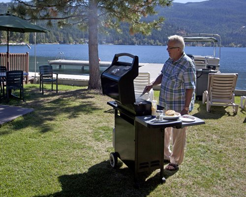 A man cooking on a barbeque grill alongside the lake.