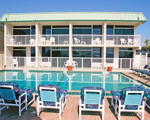 An outdoor swimming pool with chaise lounge chairs alongside multi story units.