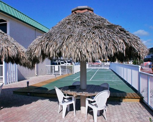 View of patio furniture with thatched sunshades.