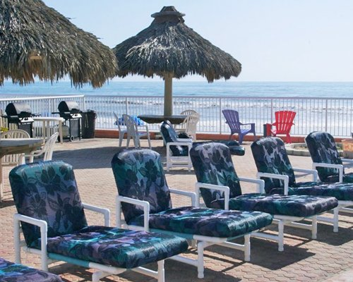 View of the chaise lounge chairs with patio and thatched sunshades alongside the ocean.
