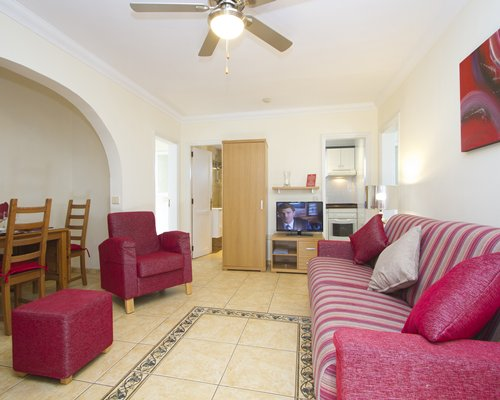 A well furnished living room with a television dining area and open plan kitchen.