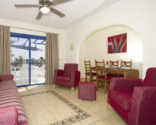 A well furnished living room with a dining area and outdoor view.