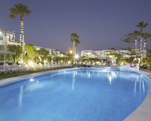 Night view of an outdoor swimming pool with chaise lounge chairs alongside the resort.