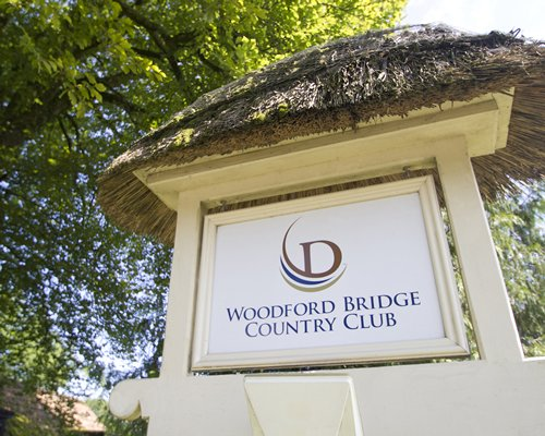 Signboard of the Woodford Bridge Country Club with a thatched sunshade.