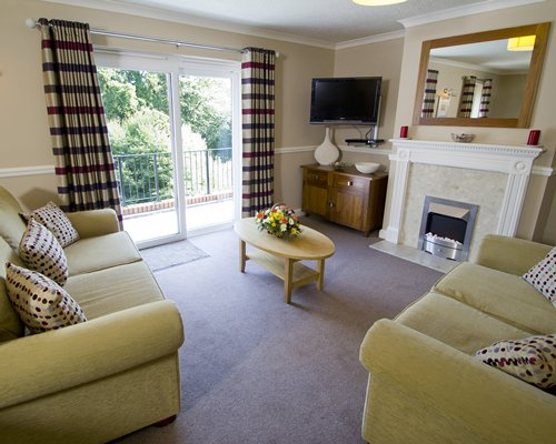 A well furnished living room with a television fireplace and balcony.