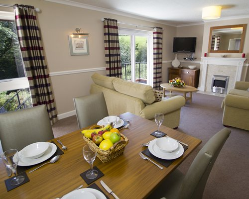 An open plan living and dining area with a television fireplace and balcony.