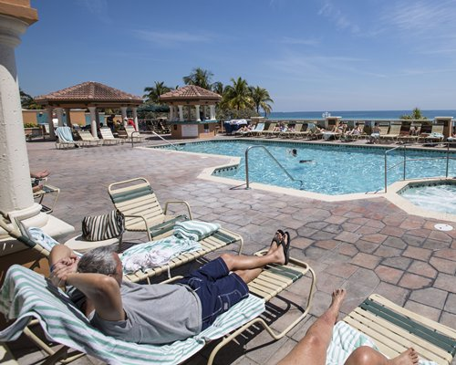 An outdoor swimming pool with chaise lounge chairs alongside the beach.