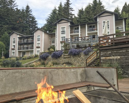 An exterior view of multi story resort units alongside a campfire.