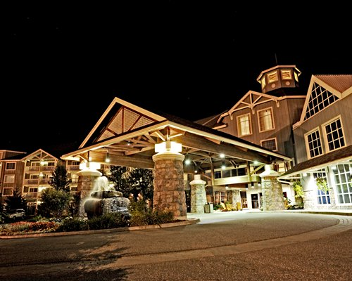 Street view of Birchcliff Villas At Deerhurst Resort with a fountain at night.