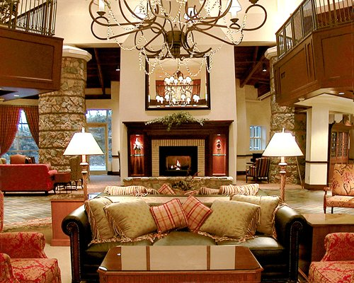 A well furnished lounge area with a fire in the fireplace.