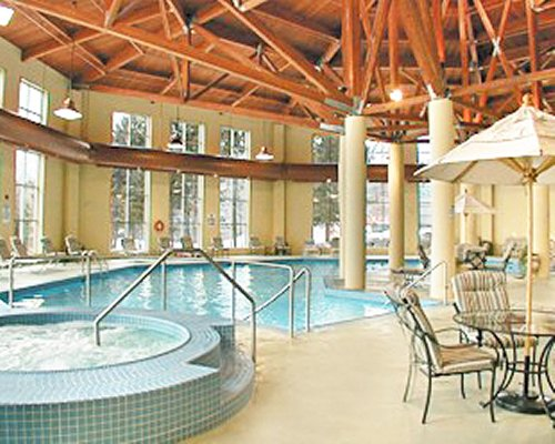 An indoor swimming pool and hot tub with patio furniture sunshades and chaise lounge chairs.