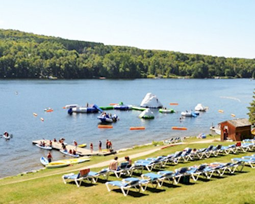 View of the lake with chaise lounge chairs and inflatable floats alongside the wooded area.