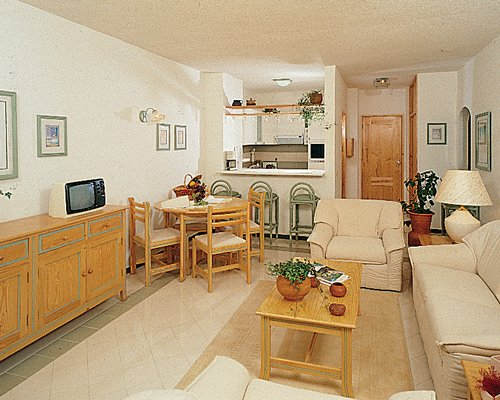 A well furnished living room with open plan kitchen breakfast bar dining area and television.