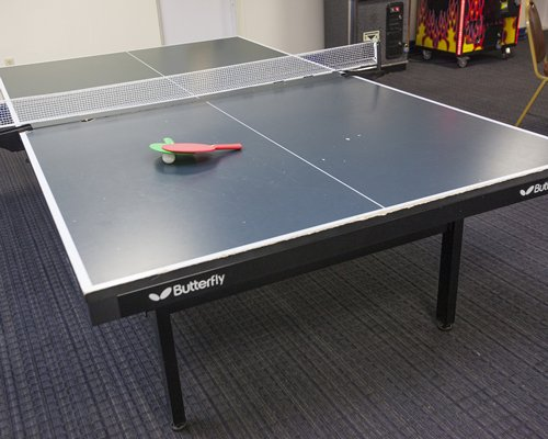 An indoor recreational room with a ping pong table.