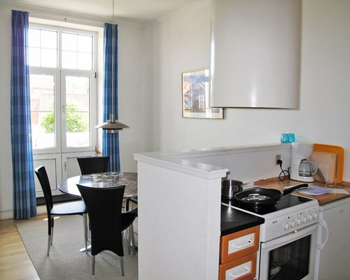 A well equipped kitchen alongside a dining area with an outside view.