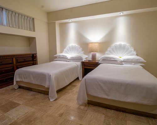 A well furnished bedroom with two beds and a balcony with the ocean view.