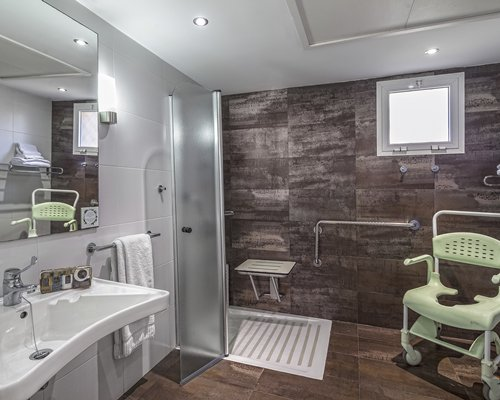 A bathroom with a single sink vanity and a stand up shower.