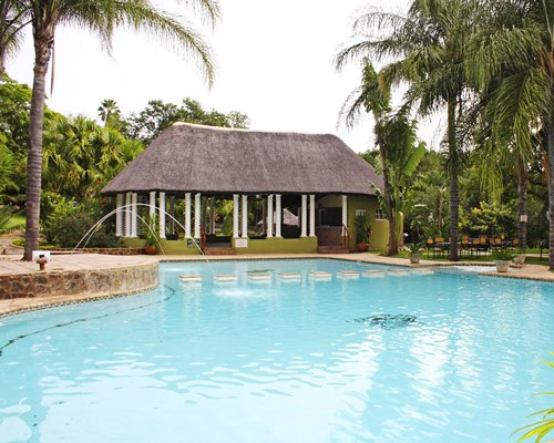 An outdoor swimming pool alongside trees and a resort unit.